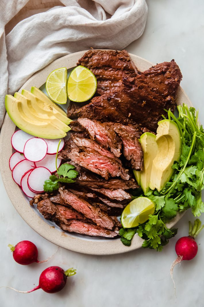 plate with sliced grilled skirt steak with avocados, radishes, cilantro, and lime