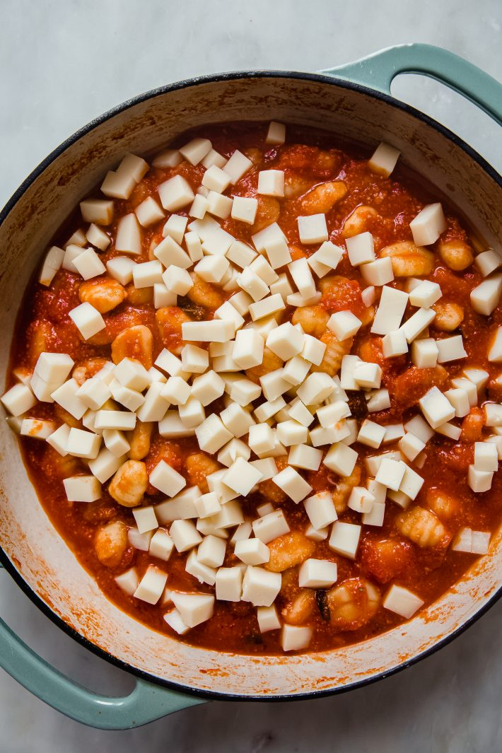 gnocchi in pomodoro topped with cubed mozzarella cheese in pan