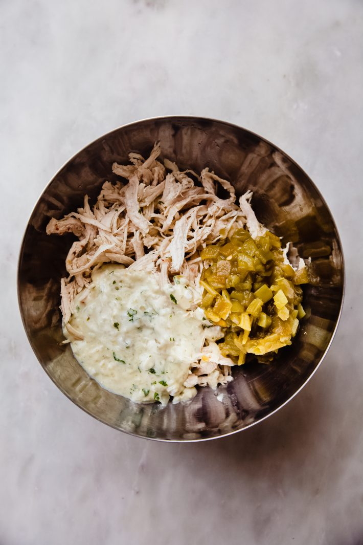 shredded chicken, diced green chilies, and cream sauce in a bowl