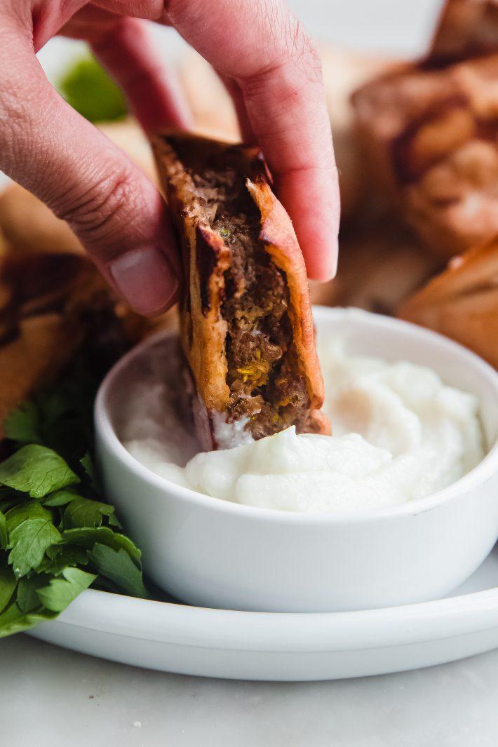hand dipping meat stuffed pita in garlic sauce