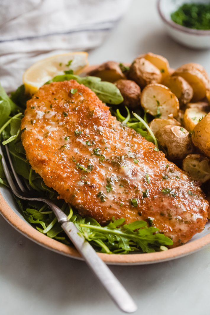 plate of chicken cutlet on a bed of arugula with roasted potatoes