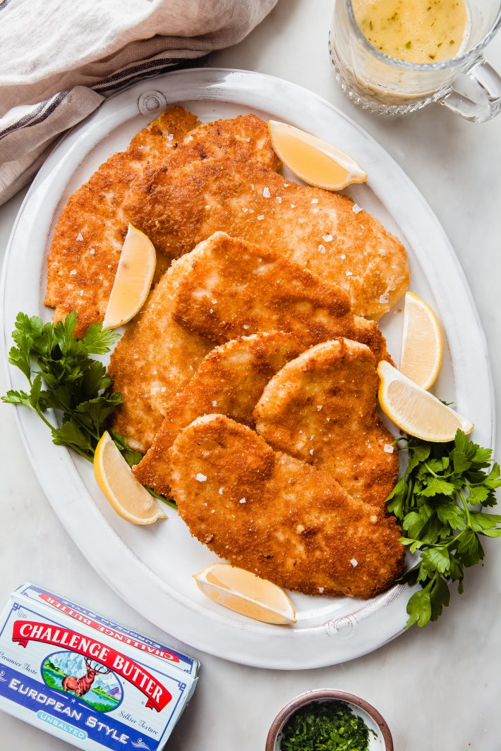 parmesan chicken cutlets on plate with lemon wedges and parsley
