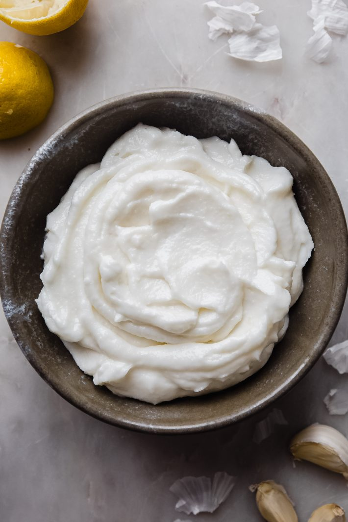 bowl of whipped garlic sauce on white marble with garlic cloves surrounding